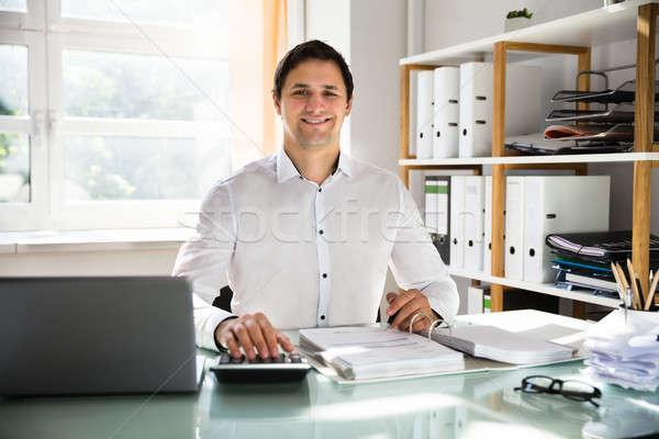 Happy businessman calculating invoice Stock photo © AndreyPopov