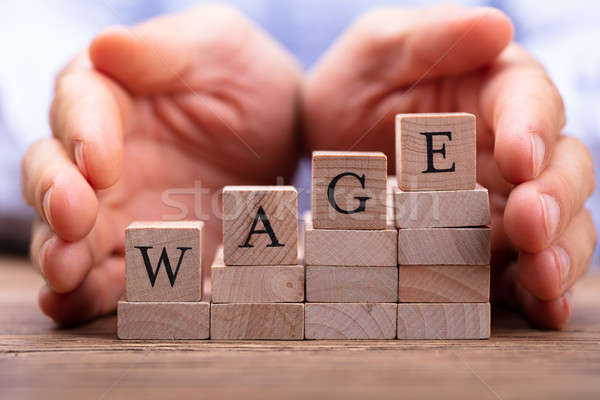 Person's Hand Protecting Wage Text On Wooden Blocks Stock photo © AndreyPopov