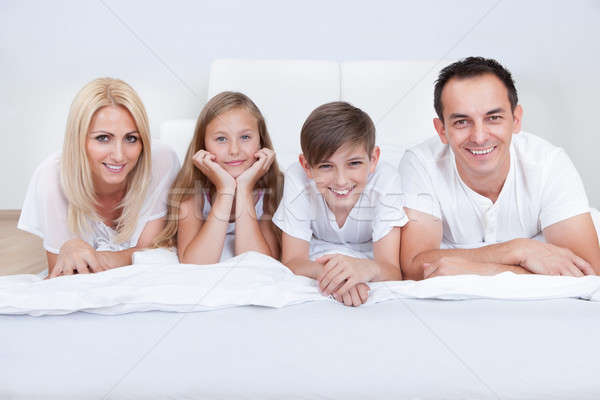 Happy Family With Two Children Lying On Bed Stock photo © AndreyPopov