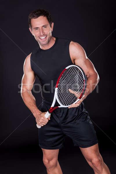 Jonge man tennisracket geïsoleerd zwarte glimlach man Stockfoto © AndreyPopov