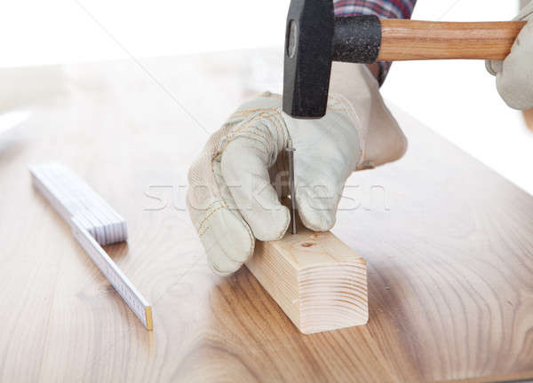 Worker hammering a nail into piece of wood Stock photo © AndreyPopov