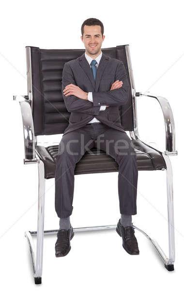 бизнесмен сидят огромный Председатель изолированный белый Сток-фото © AndreyPopov