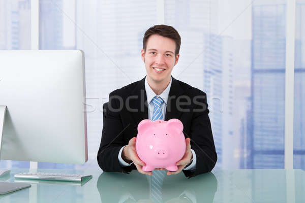 Businessman Holding Piggybank At Desk Stock photo © AndreyPopov
