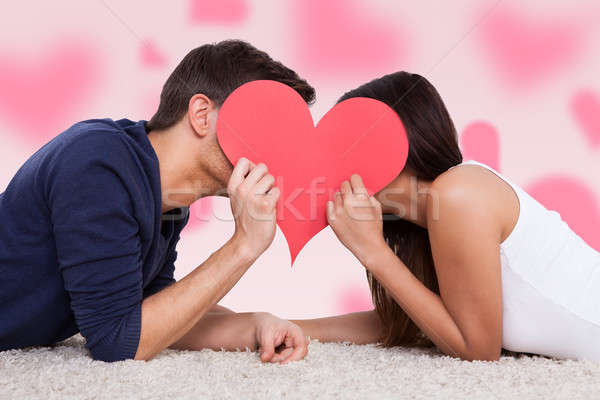 Couple Kissing Behind Heart While Lying On Fur Stock photo © AndreyPopov