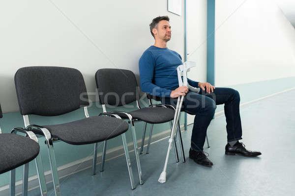 Homem sessão cadeira muletas hospital médico Foto stock © AndreyPopov