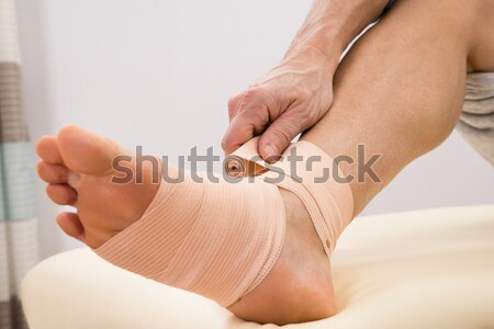 Man Putting Elastic Bandage On Foot Stock photo © AndreyPopov
