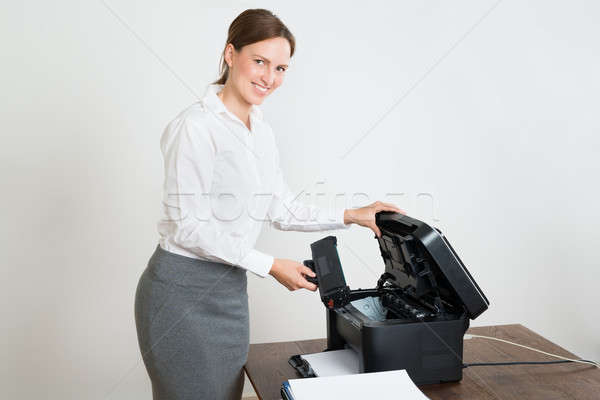 Businesswoman With Laser Cartridge And Printer At Desk Stock photo © AndreyPopov
