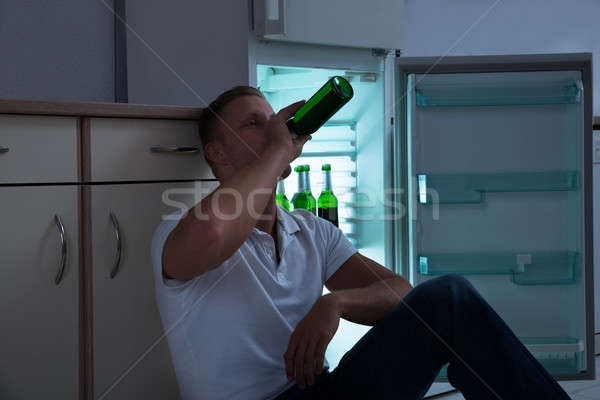 Man Drinking Beer In Kitchen Stock photo © AndreyPopov