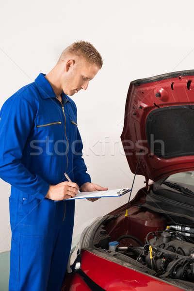Mechanic Standing Near Car Writing On Clipboard Stock photo © AndreyPopov