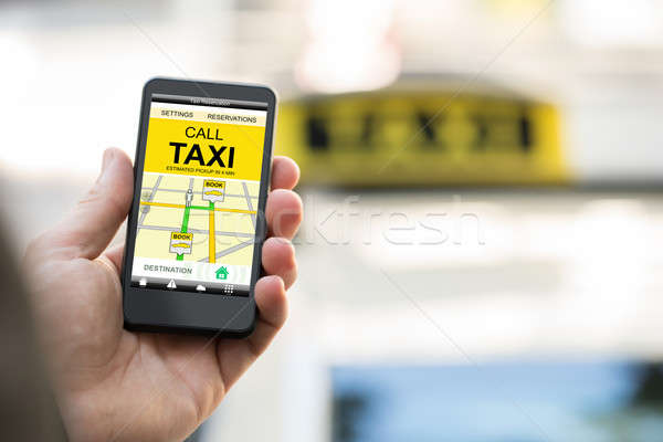 Person Booking Taxi On Smart Phone Stock photo © AndreyPopov