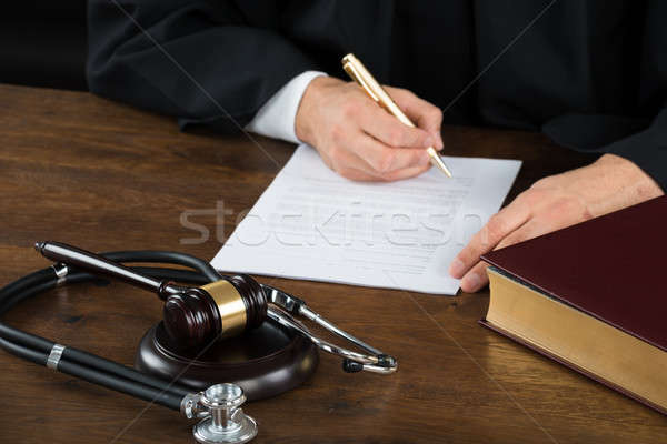 Judge Writing On Document With Mallet And Stethoscope At Desk Stock photo © AndreyPopov