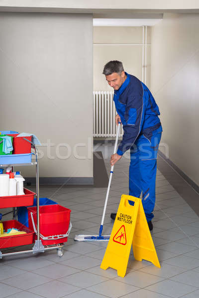 Male Worker With Broom Cleaning Corridor Stock photo © AndreyPopov