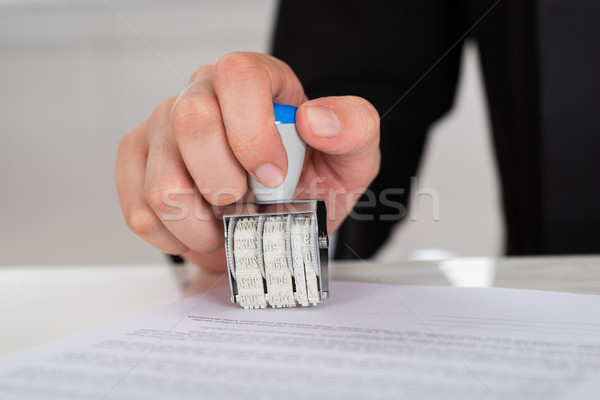 Businesswoman Stamping Contract Paper At Desk Stock photo © AndreyPopov