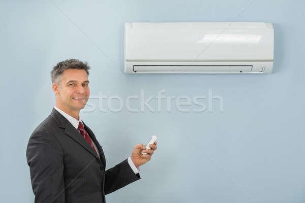 Imprenditore telecomando condizionatore d'aria ufficio maturo Foto d'archivio © AndreyPopov