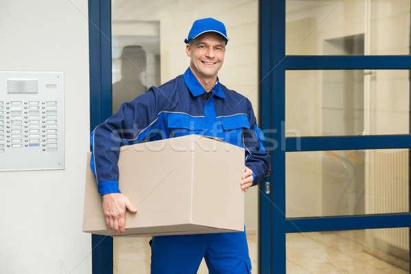 Deliveryman Standing Near Door Holding Box Stock photo © AndreyPopov