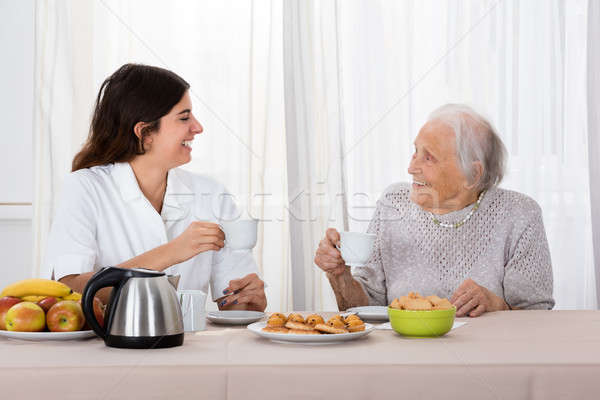 Two Women Enjoying Tea And Cookies Stock photo © AndreyPopov