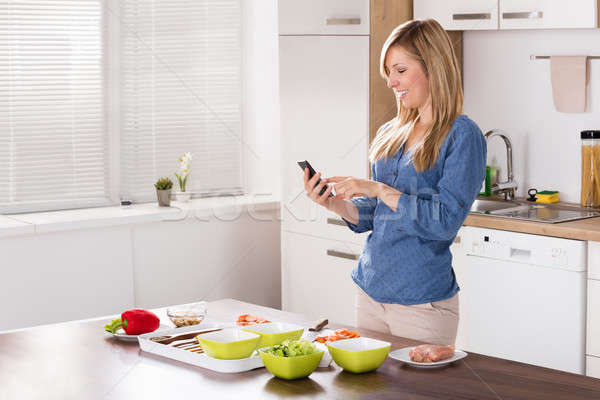 Smiling Woman Using Mobilephone In Kitchen Stock photo © AndreyPopov