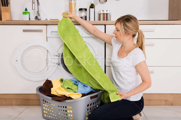 Woman Unloading Clothes From Washing Machine Stock photo © AndreyPopov