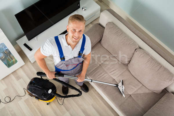 Young Man Cleaner Sofa With Vacuum Cleaner Stock photo © AndreyPopov