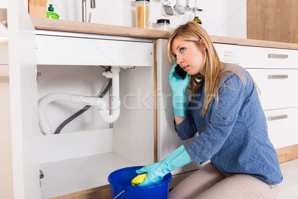 Woman Using Mobilephone Near Kitchen Sink Stock photo © AndreyPopov