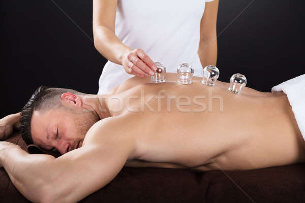 Female Therapist Placing Cups On Man's Back Stock photo © AndreyPopov