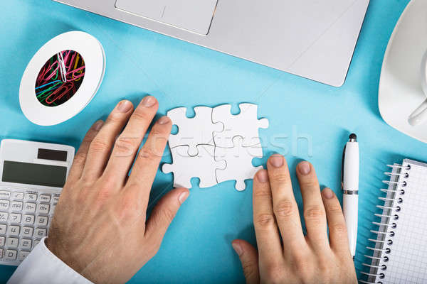 Stock photo: Businessperson Joining Puzzle On Desk