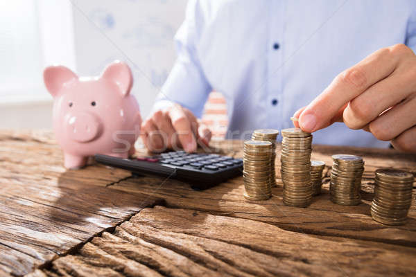 Stock photo: Person Counting Coins Using Calculator