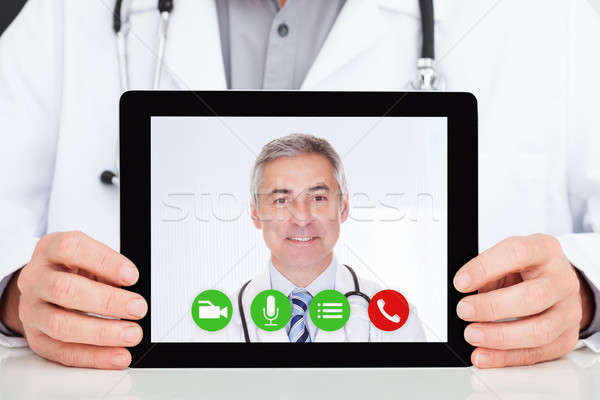 Doctor Having Conference Call With Superior On Digital Tablet Stock photo © AndreyPopov
