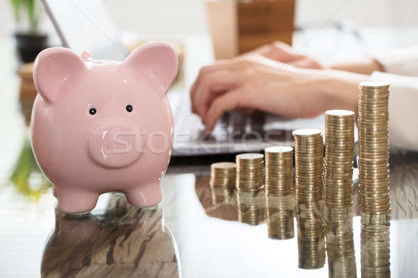 Piggy Bank And Increasing Coins Stack On Desk Stock photo © AndreyPopov