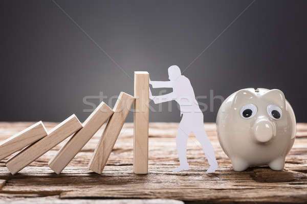Paper Man Stopping Wooden Domino Blocks By Piggy Bank Stock photo © AndreyPopov
