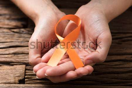 Human Hand Showing Gold Ribbon To Support Breast Cancer Cause Stock photo © AndreyPopov