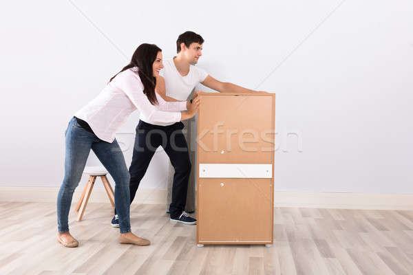 Couple Pushing The Cabinet Together Stock photo © AndreyPopov