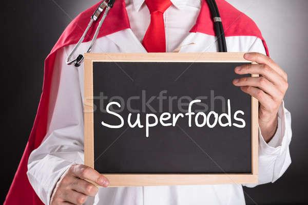 Superhero Doctor Holding Small Chalkboard Stock photo © AndreyPopov