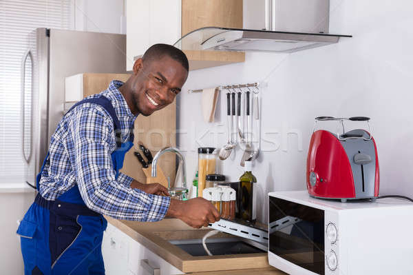 Man In Overall Checking Induction Stove Stock photo © AndreyPopov