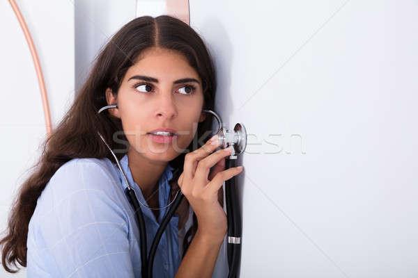 Ciekawy kobiet słuchania ściany młodych kobieta Zdjęcia stock © AndreyPopov