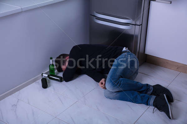 Man Lying On Floor In Kitchen Stock photo © AndreyPopov