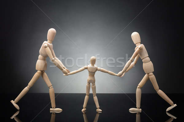 Wooden Figure Parents Pulling Child Dummy Against Each Other Stock photo © AndreyPopov