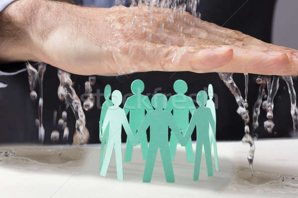Hand Protecting Paper Cutout Human Figures From Water Stock photo © AndreyPopov