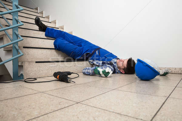 Handyman Lying On Staircase Stock photo © AndreyPopov