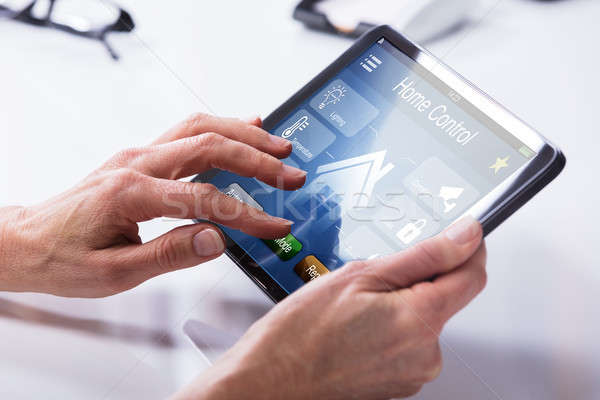 Person Using Home Control System On Digital Tablet Stock photo © AndreyPopov
