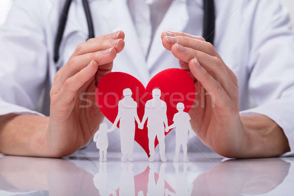 Doctor Protecting Family Cut Out With Heart Shape Stock photo © AndreyPopov