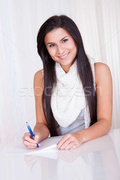 Woman sitting writing notes Stock photo © AndreyPopov