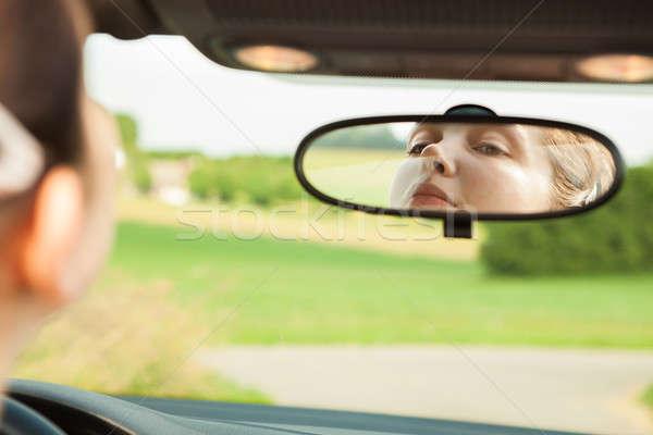 Donna guardando specchio auto guida Foto d'archivio © AndreyPopov