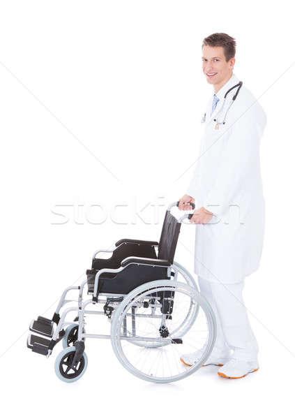 Foto stock: Jovem · médico · do · sexo · masculino · empurrando · cadeira · de · rodas · branco · homem