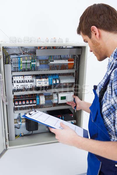 Technician Holding Clipboard While Examining Fusebox Stock photo © AndreyPopov