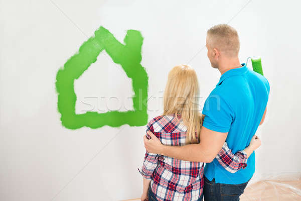 Couple Standing Front Home Painted On Wall Stock photo © AndreyPopov