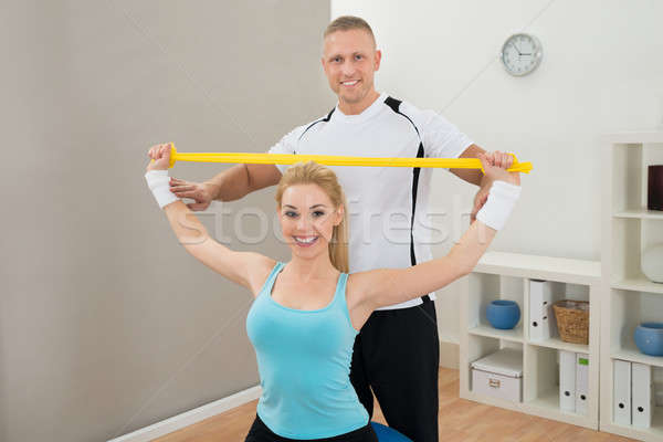 Instructor Standing Behind Woman Exercising Stock photo © AndreyPopov