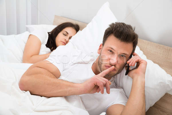 Stock photo: Man Talking Privately On Cellphone