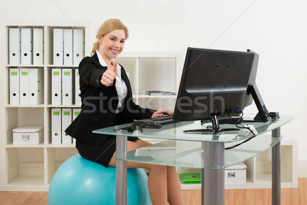 Businesswoman On Pilates Ball While Using Computer Stock photo © AndreyPopov