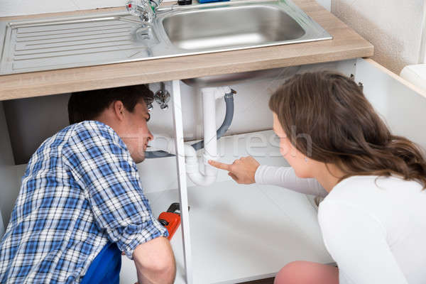 Woman Showing Damage In Sink Pipe To Plumber Stock photo © AndreyPopov